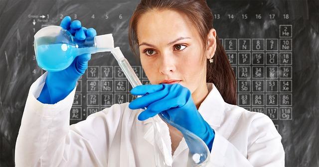 Frau mit Laborkittel füllt Flüssigkeit um.
