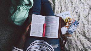 Stift und Buch auf Oberschenkeln liegend
