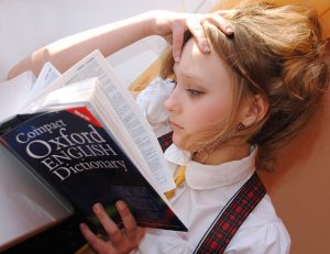 Mädchen, das in einem englischen Lexikon blättert und lernt.