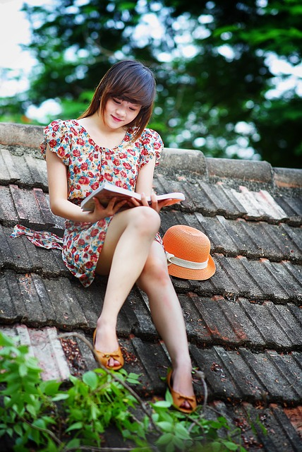 Mädchen liest auf einem Dach sitzend.
