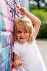 Mädchen lehnt an einer bunten Wand und lächelt.