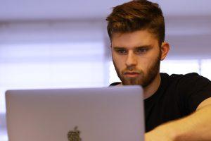 Mann arbeitet am Laptop.