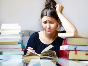 Frau, die verzweifelt in einem Buch liest.