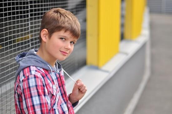 Junge mach Pause und lehnt an Mauer