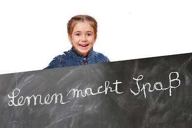 Kind an einer Tafel mit der Aufschrift Lernen macht Spaß!