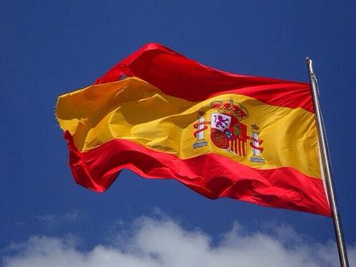 Flagge Spaniens im Wind vor blauem Himmel