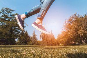 Springen über einen sonnigen Rasen