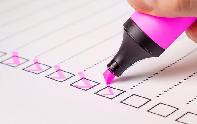 Checkliste, Ausschnitt eines Blatts Papier, Haken mit rosa Markierungsstift geschrieben