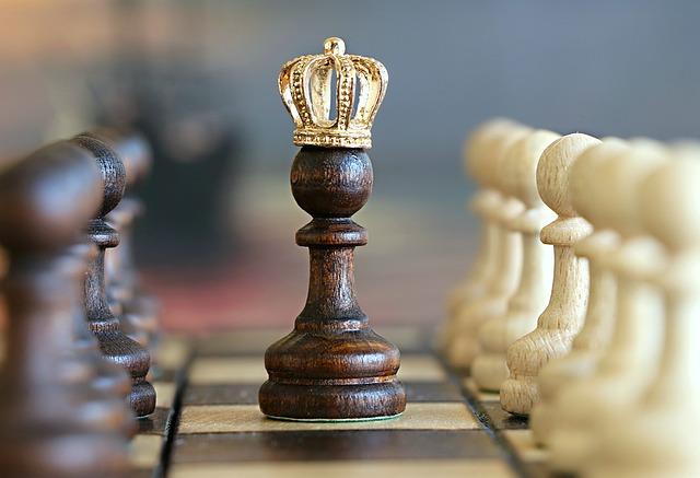 Schachfigur mit einer goldenen Krone zwischen zwei Reihen von Bauern