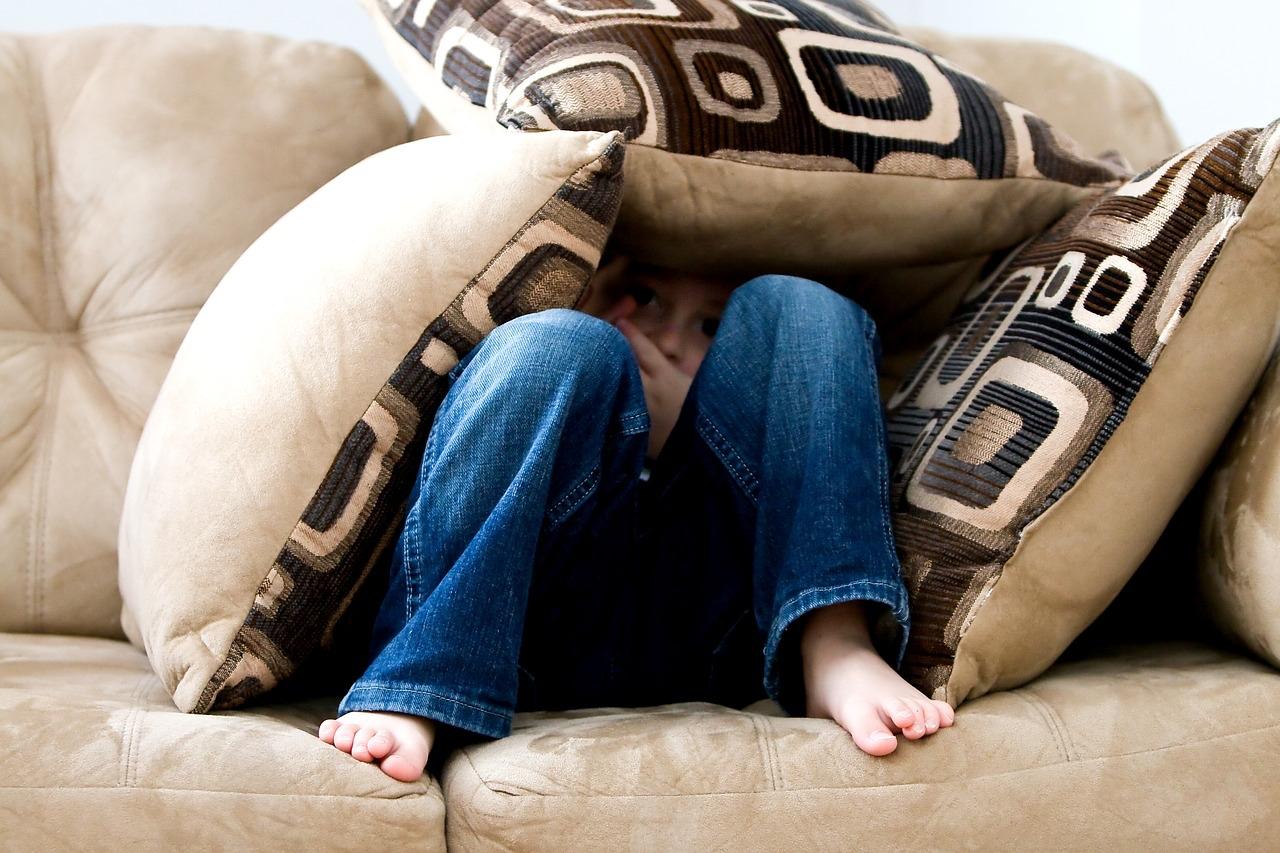 Kind auf Sofa eingehüllt von Sofakissen, ängstlich