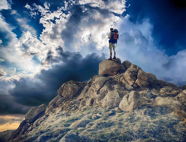 Mann auf Gipfel im Gegenlicht. Sonne scheint durch mittelhohe Wolken.