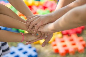 Hände von sieben Kindern halten sich gegenseitig.