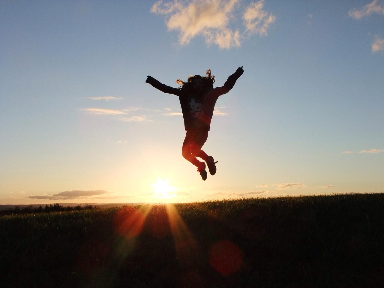 Frau springt bei Sonnenuntergang in die Höhe mit ausgestreckten Armen, im Gegenlicht