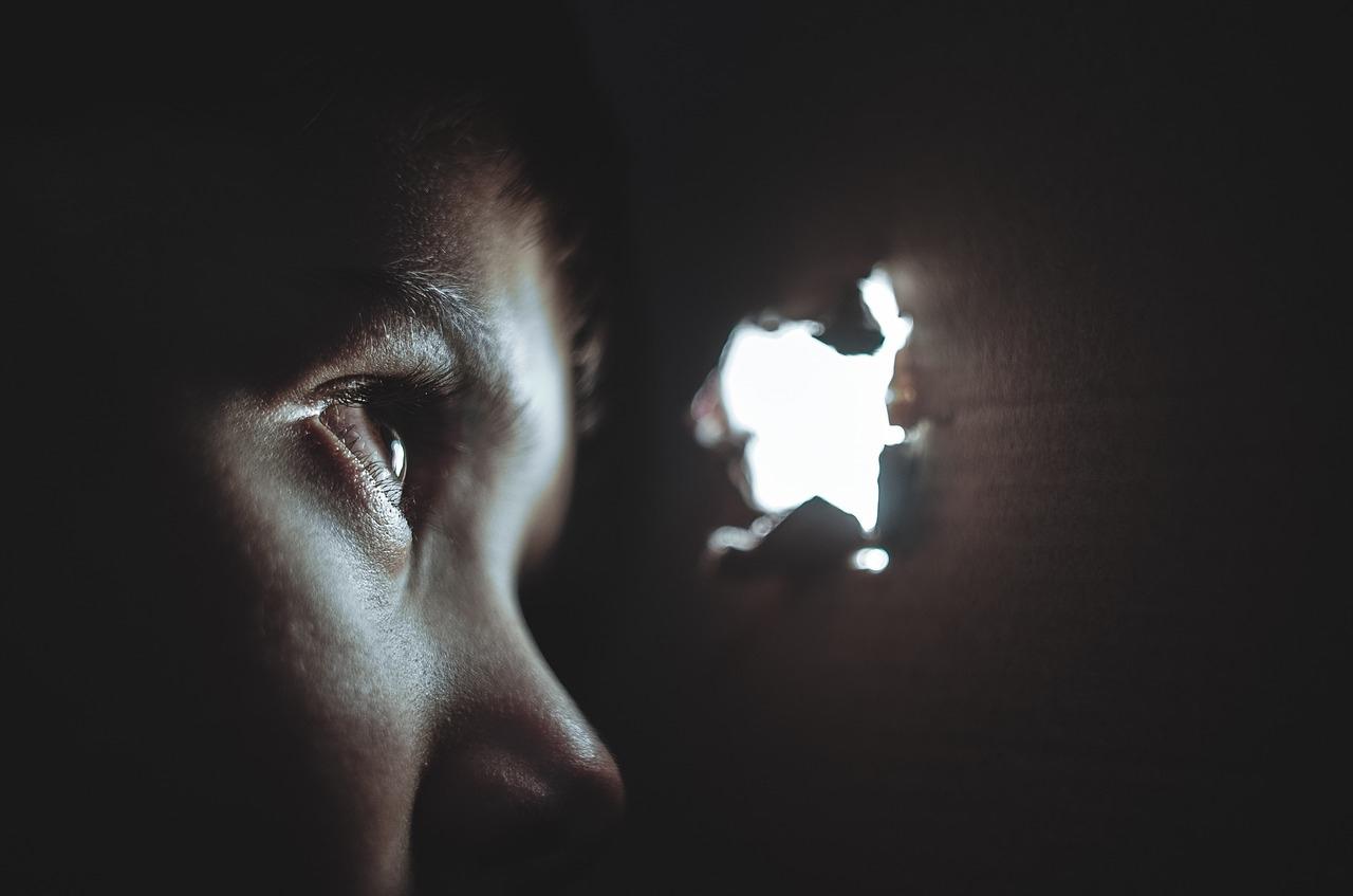 Kind schaut unsicher durch ein Loch in der Wand. Selbst im Dunkeln, außen ist Licht.