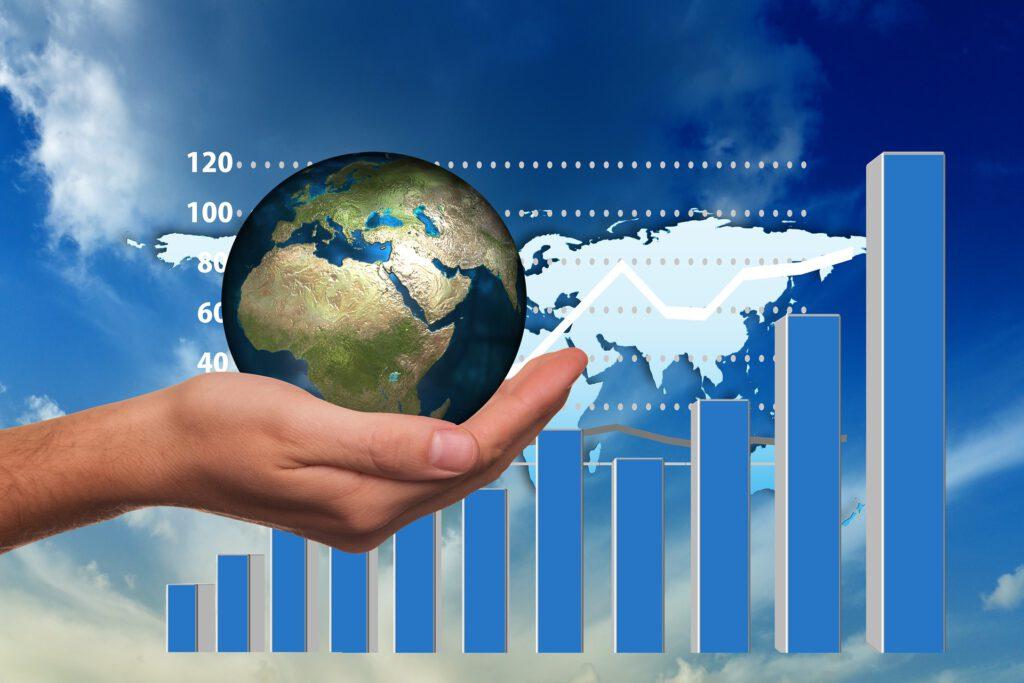 Balkendiagramm blau aufsteigend vor Weltkarte. Hand im Vordergrund hält Weltkugel