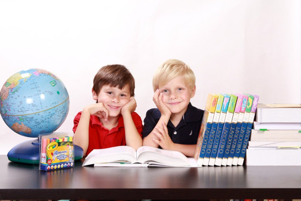 2 Jungs  schauen lächelnd in die Kamera. Auf dem Tisch sind Bücher und ein Globus