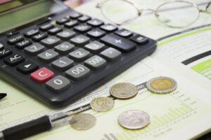 Taschenrechner und Münzen liegen auf einem Tisch