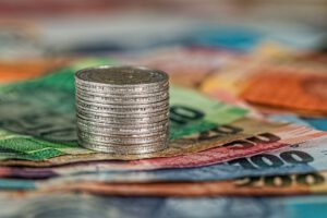 Euromünzen aufgetürmt,  stehen auf mehreren Euroscheinen