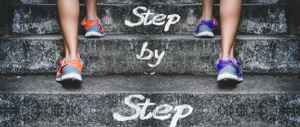 """Füße in Sportschuhen, die eine Treppe nach oben gehen. Text auf den Treppen """"Step by Step"""" (Schritt für Schritt)"""